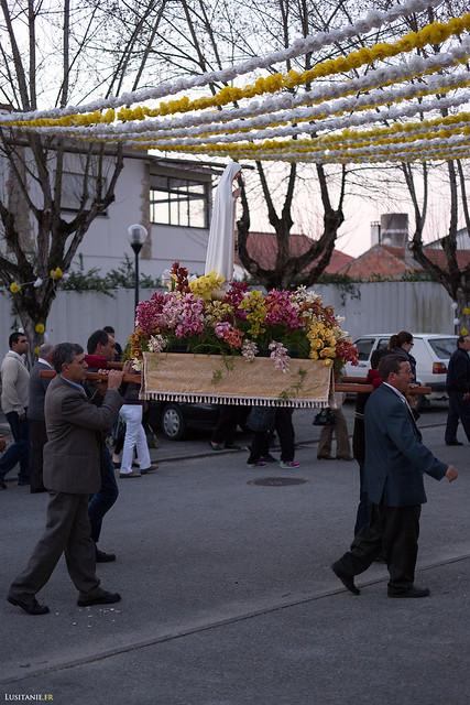 Quatre hommes portent l'image de la Vierge Marie, parée de fleurs.
