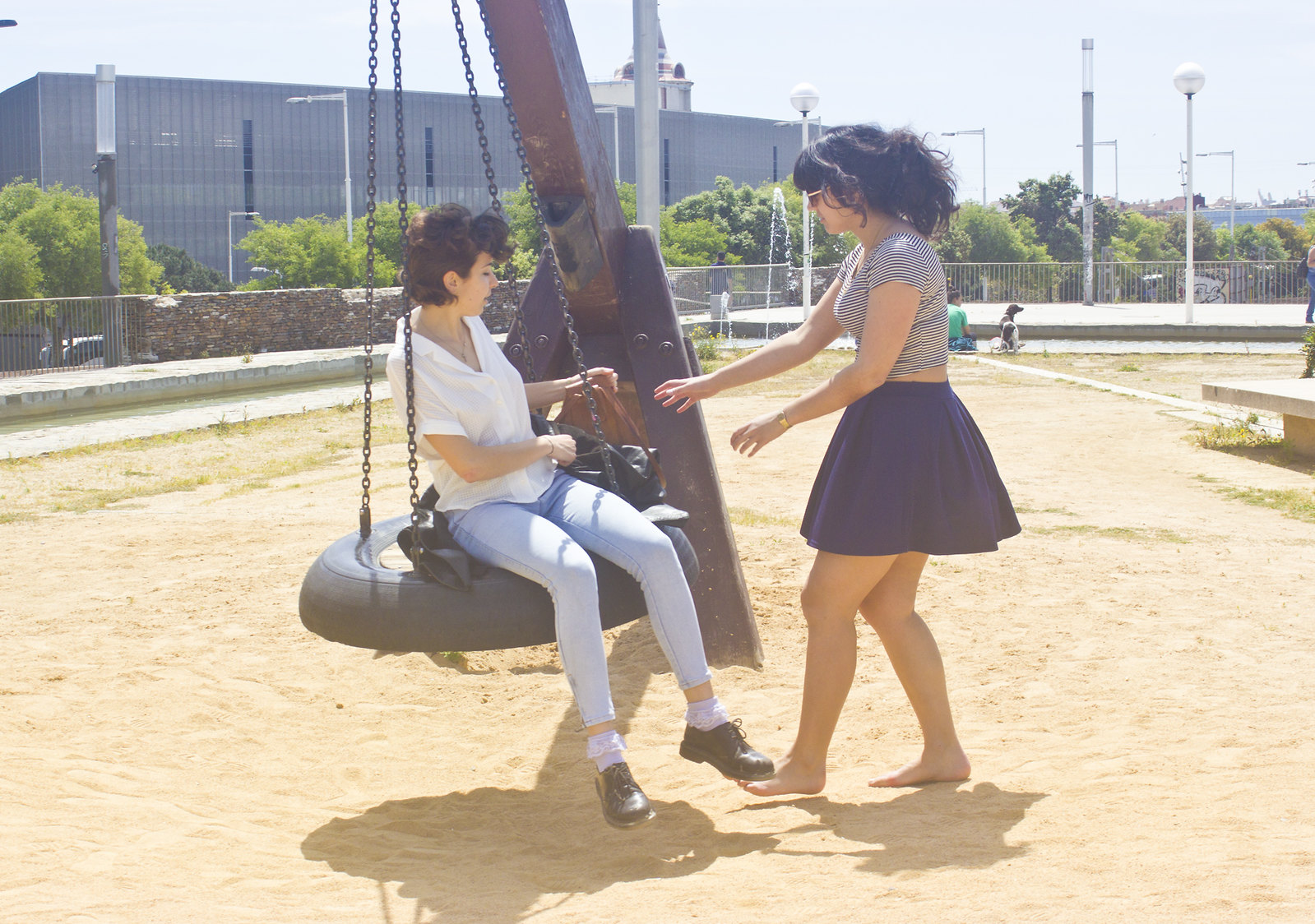 Girls in playground on giant tyre swing barcelona