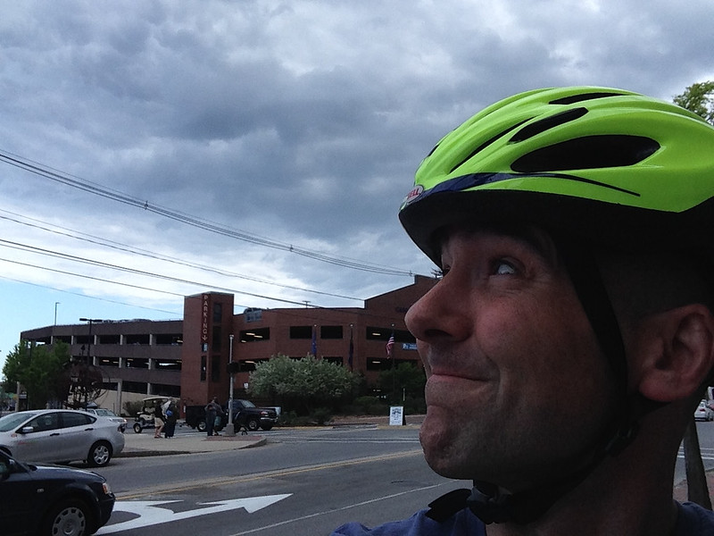 Brian in a bicycle helmet with rain clouds in the background.