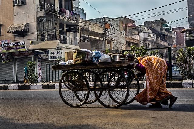 Old woman pushing cart