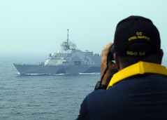 Cmdr. Joe Femino, commanding officer of USS Curtis Wilbur (DDG 54), watches USS Freedom (LCS 1) as the ships pass June 20 during a divisional tactics drill as part of Cooperation Afloat Readiness and Training (CARAT) Malaysia 2013. (U.S. Navy photo by Chief Mass Communication Specialist Matthew Olay)