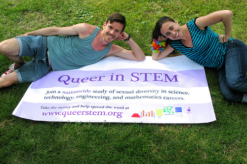 Yoder and Mattheis doing some last-minute recruiting for their survey at the Twin Cities Pride Festival earlier this year, laying on a flag that says Queer in STEM