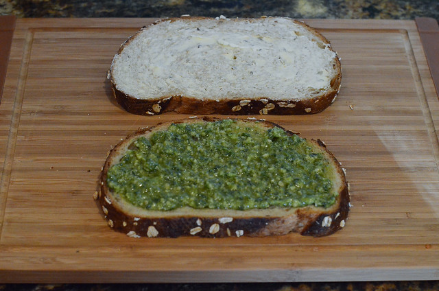 One of the slices of bread is spread with pesto.