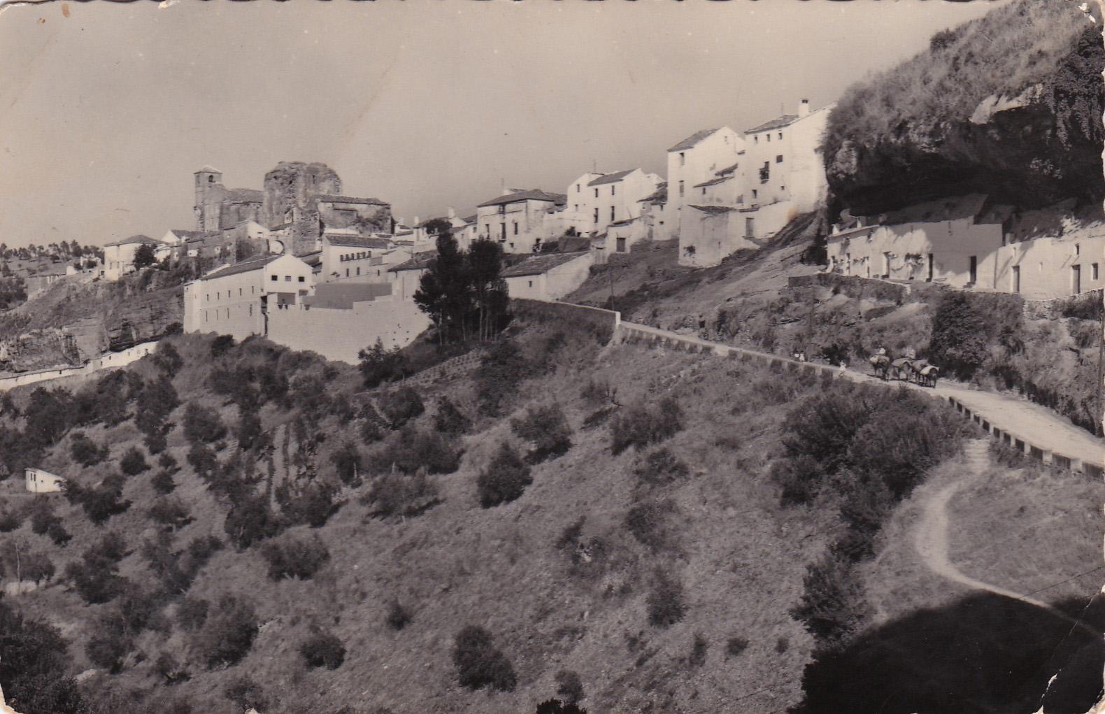 """Imagen de Las Calañas, con el camino hacia Los Caños visible y al fondo el cine de verano, en el actual Hotel Villa de Setenil. Todavía no se han construido los """"pisos de los maestros"""" y la presencia de los burros es constante."""