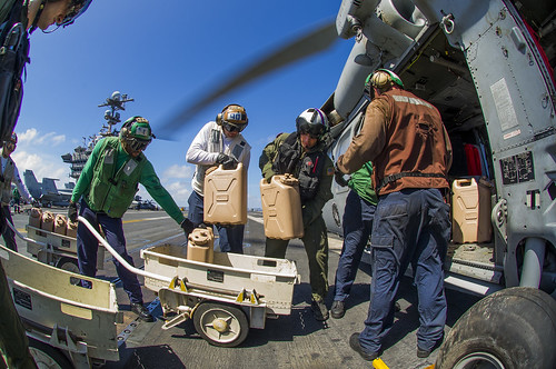 Sailors aboard the aircraft carrier USS George Washington (CVN 73) load containers of fresh water