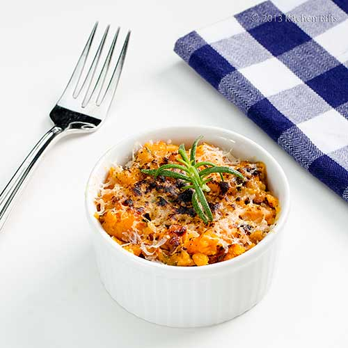 Sweet Potato and Rosemary Casserole in ramekin with fork and napkin in background