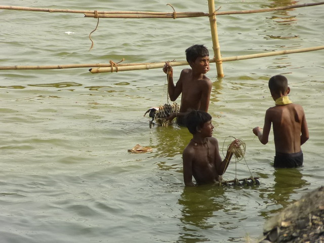 Boys standing in the river holding the magnets used to collect coins