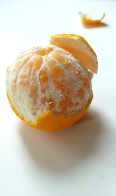 Peeled orange on white (well, a mandarin actually)