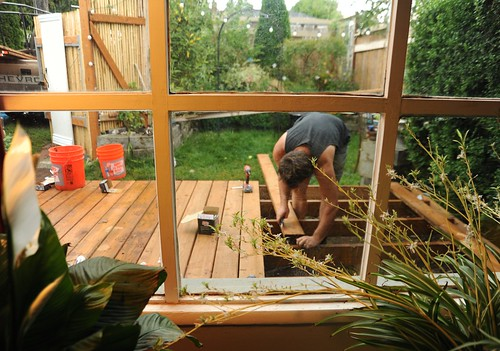Stephen finishing the new deck, working with treated 2 by 4's, through the window, peace plant and spider plants, orange buckets, chevy truck, A Garden for the Buddha, Seattle, Washington, USA by Wonderlane
