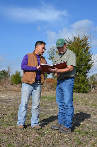 David Pi of Houston and Phillip Stewart, NRCS district conservationist in Liberty, Texas, discuss locations for future brush clearing and grass planting on Pi's 39 acres.