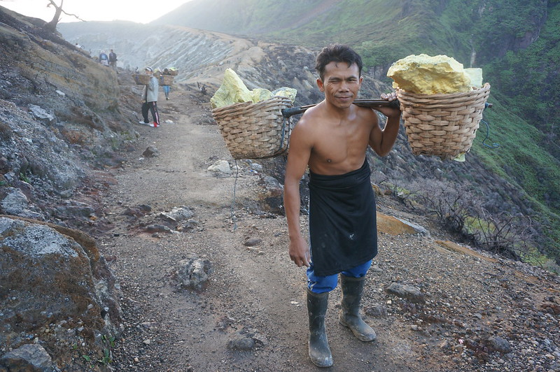 Local miner carrying heavy sulphur rocks from the Ijen crater
