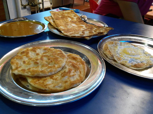 Clockwise from top: curry prata, plaster prata, and prata kosong