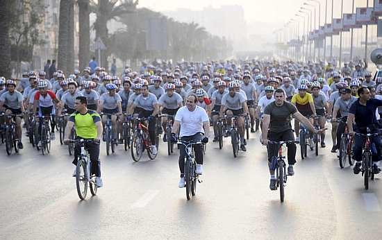 Presidente do Egito, Abdel Fattah al-Sisi (de camiseta branca) anda de bicicleta com centenas de egípcios, nos arredores do colégio militar no Cairo, nesta sexta-feira, 13 de junho - Reuters