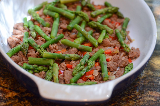 The cooked ground turkey and asparagus are layered in a casserole dish.