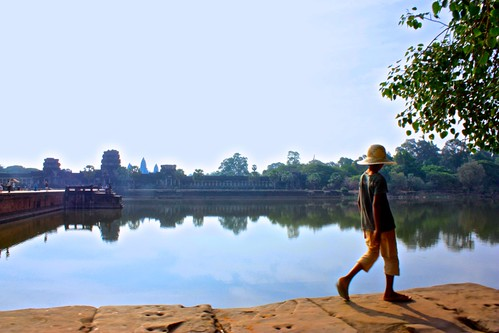 A local teenager walks along the moat wall outside of Angkor Wat