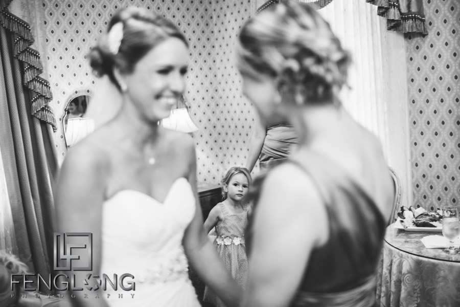 Flower girl looks on as bride puts on her wedding dress