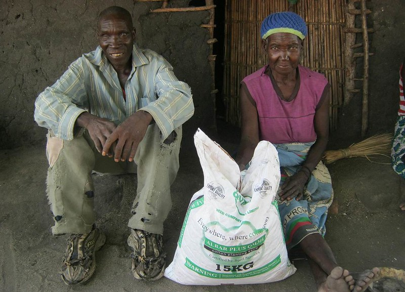 Robert and Dorica seated outside their house, with 5kg of cotton seed which they were provided.