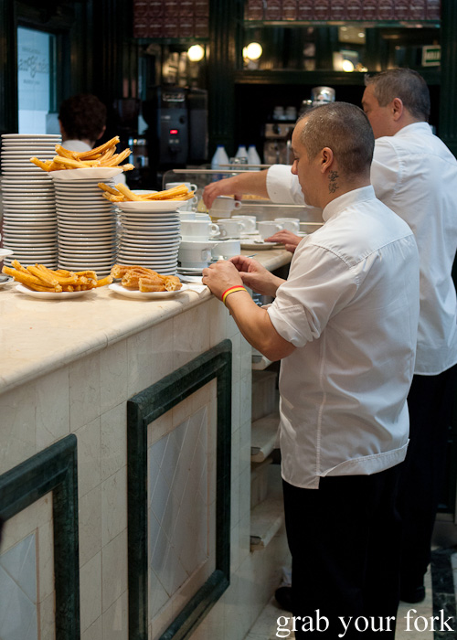 Waiters picking up churros orders at Chocolateria San Gines in Madrid, Spain
