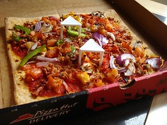 "A square pizza in a cardboard box with ""Pizza Hut Delivery̦"" written on te front. There are two little triangular white plastic things stuck in the pizza to stop the lid collapsing on it when closed. Pieces of red onion, green pepper, and other vegetabls are visible on the pizza."