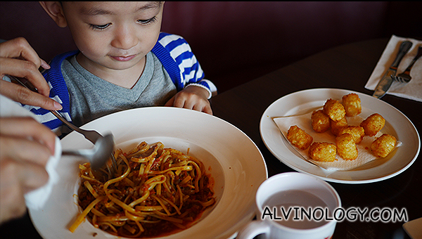 Digging into a kid-sized serving of linguine bolognese at Au Chocolat