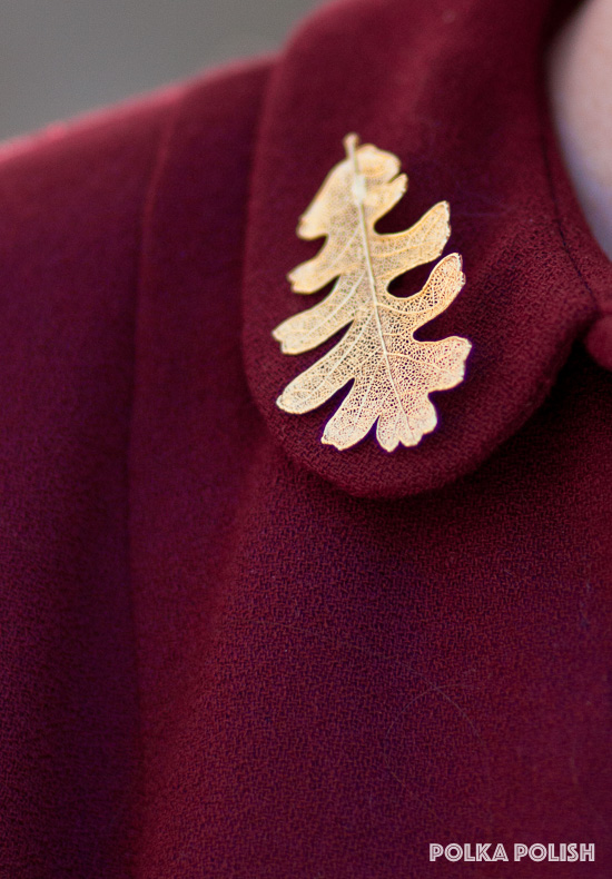Skeletonized gold Quercus lobata valley oak leaf brooch on the collar of a deep red vintage jacket