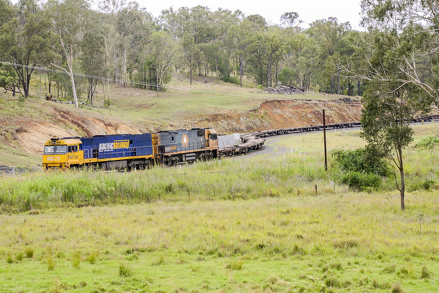 Pacific National NR73+NR32 sit in the Bromelton Blue Metal siding with a rake of empty container wagons