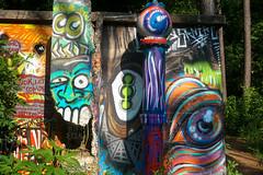 outdoor structure(0.0), sculpture(0.0), urban area(0.0), tiki(0.0), totem pole(1.0), art(1.0), graffiti(1.0),