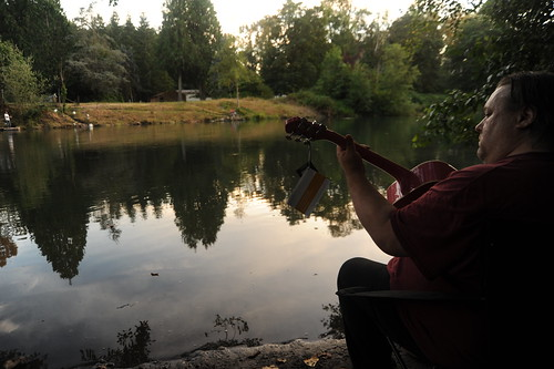 Billy breaks in Pinky, a new 3/4 size Washburn guitar with tags still attached, down by the Nisqually river, reflection of trees, summer evening, Nisqually, Washington, USA by Wonderlane
