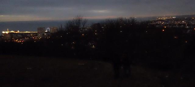 Walkers descending towards the bright lights