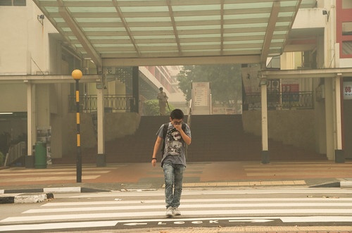 A boy covering his nose while crossing the streets near Bukit Merah Central - the PSI has reached a high of 400 in this small city state, reaching hazardous levels.