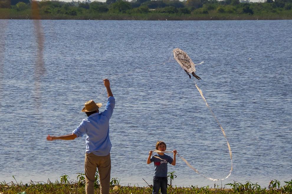Padre e hijo hacen volar una pandorga en la costanera, que los fines de semana atrae a miles de personas que acuden a caminar, pasear, andar en bicicleta o disfrutar del aire libre en este nuevo espacio que se está convirtiendo en una gran atracción de Asunción.  (Tetsu Espósito).