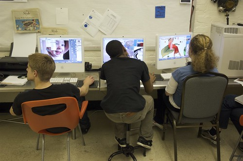 Three students at computer workstations, seen from behind