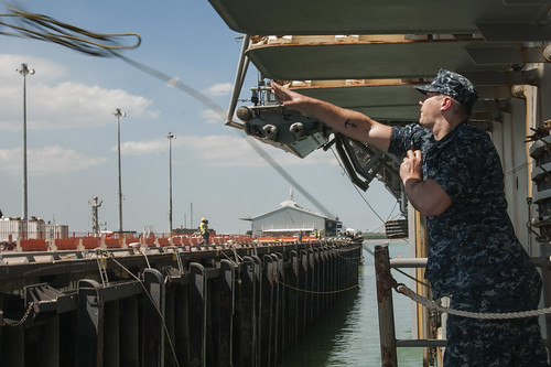 Seaman Jeremiah Baker throws a messenger line from the forward-deployed amphibious assault ship USS Bonhomme Richard (LHD 6)