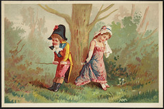 Girl and boy in historical costume facing away from each other by a tree trunk. The boy is holding a stick, the girl is holding a handkerchief. [front]