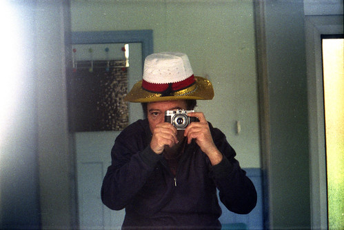 reflected self-portrait with Agilux Agimatic camera and three hats by pho-Tony