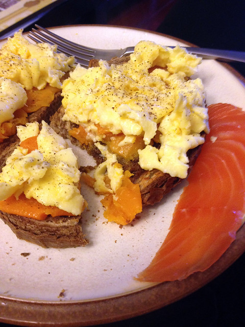 Scrambled eggs with mashed squash on toast, with cured salmon.
