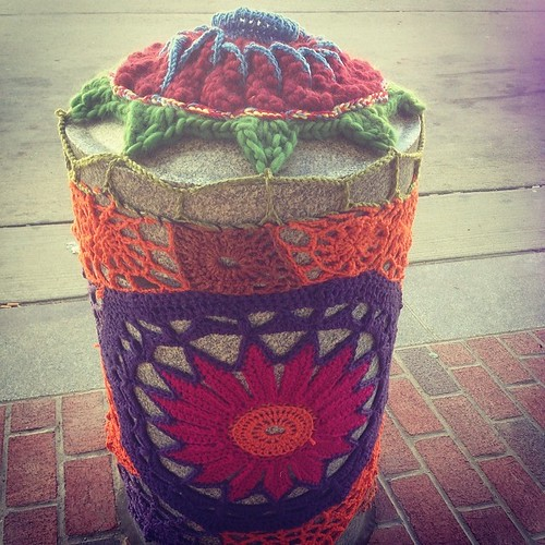 One of the  yarn bomb pylons with my daisy on the bottom #accbaltimore #baltimorethreadquarters