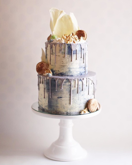 I've been dying to do a funky drip wedding cake and today was the day. Swiss meringue buttercream cake with dark blue accents. Grey drip. Torched meringue. White chocolate sail on top. French macaron and candy accents. The cake was a dark chocolate cake w
