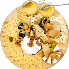 cheese platter with nuts and honey on a plate