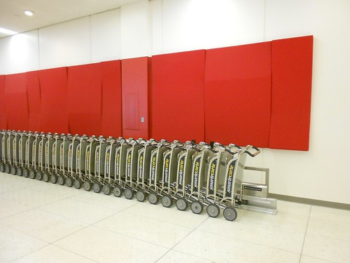 Endless pay-per-use baggage carts lined up on a money-sucking track below an art installation of red, slanted-surface rectangles.