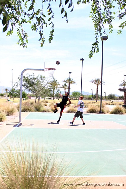 Two boys playing basketball in the summertime.
