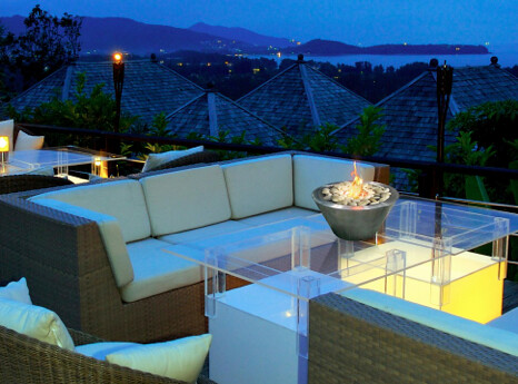 mopdern wicker outdoor sofa seat on patio at night