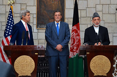 U.S. Secretary of State John Kerry, joined by United Nations Assistance Mission in Afghanistan head Jan Kubis, listens as Afghan President Hamid Karzai addresses reporters on the Presidential Palace Grounds in Kabul, Afghanistan, on July 12, 2014, about a deal on a technical and political plan the Secretary helped broker to resolve an election dispute between rival presidential candidates Ashraf Ghani and Abdullah Abdullah. [State Department photo/ Public Domain]