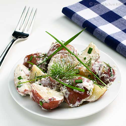 Horseradish Potato Salad on plate with chives and dill garnish