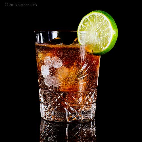 Cuba Libre Cocktail with Lime Garnish, on black acrylic