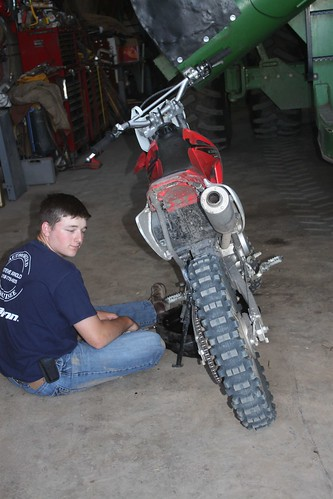 Brandon changing oil on his dirt bike. He missed all his toys.