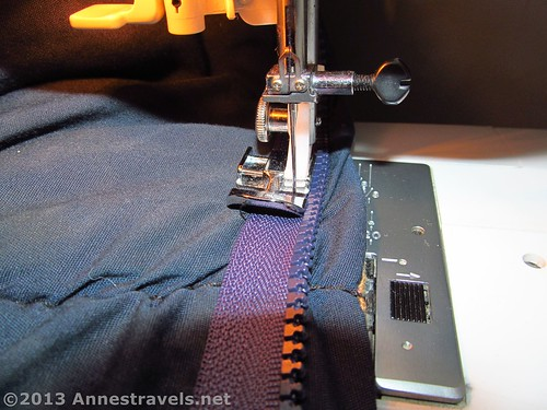 Sewing a new zipper into a sleeping bag to replace a broken zipper.