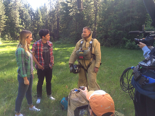"U.S. Forest Service smokejumper Greg Fashano talks with Taryn Brooks and Golan Yosef of Disney Channel's ""Movie Surfers"" after landing in a small meadow at Slate Creek on the Shasta Trinity National Forest in California. (U.S. Forest Service/Leo Kay)"