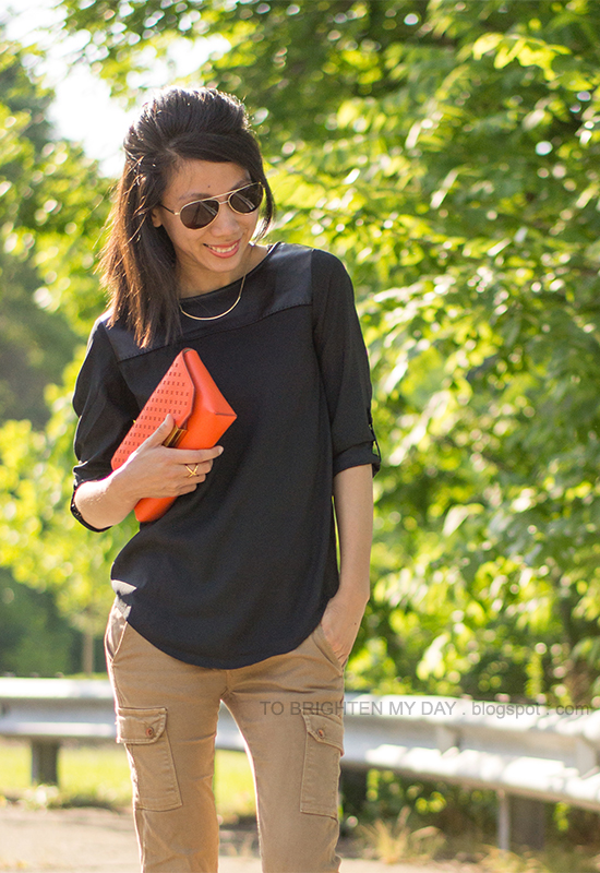 black faux leather yoke top, cargo pants, orange clutch