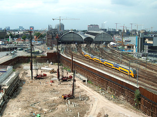 View over the last excavation of Oosterdok building with rusty sheet pilings and ramming of concrete pilings and the Central Station on the horizon with the caps, Amsterdam center; urban photography in the Netherlands, Arjan Heijnsbroek, 2007